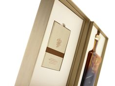 The box was crafted using complex rigid board construction, and is wrapped in bespoke paper stock, debossed with a fine wood grain effect. On the front of the case, the John Walker & Sons monogram is displayed in deep copper foil. Providing a striking contrast is the silver foil Royal Warrant emblem. The whisky bottle is held snugly in a fitted recess in the main body of the case, and can be easily slipped out with an attached copper ribbon. Opposite rests a hardback information booklet.