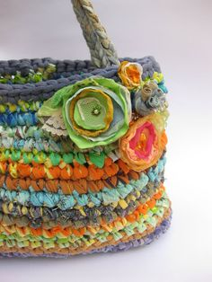 Happy, colorful handbag. Handmade from recycled materials, plarn (plastic bags yarn) and scraps fabric yarn that I make myself. Colorful fabric flowers,