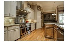 Gorgeous- white outer cabinets, darker wood island, and stainless and granite all over
