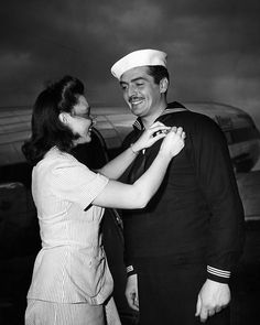 American actor and Coast Guardsman Victor Mature receiving campaign ribbons from Juanita Ferrara, the Coast Guard Public Relations Secretary, 1943.