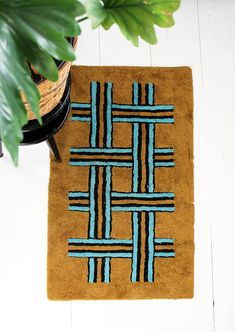 Heard you like weaving so we put a weave on a weave. Rya-style rug with medium-pile shag on cotton fabric backing in gold, black, and turquoise. Bottom side mirrors front for a neat embroidered effect. There are a few small patches on the front where the cotton padding/lining shows through