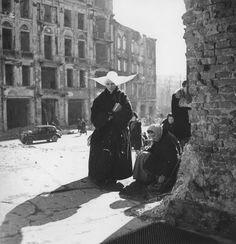 Warszawa - siostra zakonna przed zrujnowanym wejściem do dolnego kościoła św. Krzyża (marzec 1945)