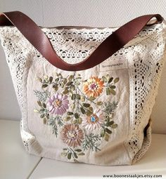 This adorable floral shoulder bag is made of vintage hand embroidered ecru linen with a crochet border. Just the bag for boho lovers! Bag closes with a strong zipper and has three pockets inside. Lined with brown heavy cotton. The repurposed leather strap is 18,5 / 47 cm long One of a king item!!!!! size: wide: 15 / 28 cm high: 13 / 23 cm deep: 7 / 18 cm thanks for visiting my shop: www.etsy.com/shop/boonestaakjes