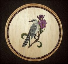 This Bird Wall Dcor, Mockingbird  Iris Blossoms Embroidery Wood Art combines the warmth of wood with the raised texture of 18 different thread colors, and 17,343 stitches. The design was machine embroidered into a sheet of balsa wood, then cut and mounted on an oak stained 6-3/4 diameter round plaque. The brown leather braided trim was added before a clear protective, non-yellowing acrylic matte finish was applied. A brass hanger is attached to the backside making it ready for hanging.  ...