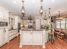 Kitchen with distressed antique white cabinets, custom island and red oak floors