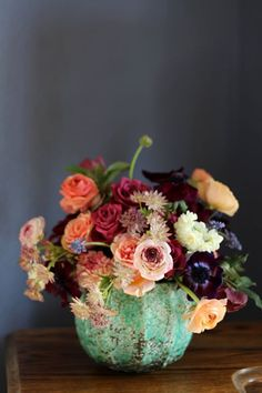 Pretty mix of flowers-- anemone, roses, ranunculus. Aqua, burnt orange, amethyst, burgundy, champagne colors