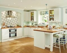 Shaker kitchen in White. Love the wooden counter tops and the recess above the stove