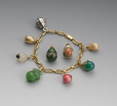 Russian gold bracelet w/seven mini Easter eggs, circa 1900. A Fabergé gold & translucent pale-orange enamel egg, front set with diamond; a chrysophase & gold egg applied w/4 diamonds (F.R.); a translucent pink enamel egg with a flower set w/diamonds & seed pearl (A*H); a nephrite elephant, eyes set w/diamonds, possibly Michael Perchin; a rock crystal egg set with cabochon sapphire, marked K.F.; a gold egg; and a silver egg; the gold bracelet marked V.S., St. Petersburg, 1899-1908.