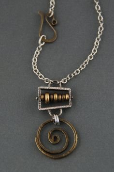 A solid brass spiral hangs below a heavily textured sterling silver abacus, accented with brass beads. The pendant hangs from a stainless steel chain,