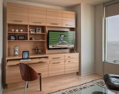This multi-functional space provides accommodations for guests, acts as an in-home office and functions as a retreat for boys to enjoy media entertainment. The room has little closet space, so an appropriate storage solution was designed to meet all the needs. The wood selection complements the homeowner's contemporary taste but doesn't detract from the view. Grain patterns, matched to perfection, offer subtle interest. Doors are flush and clean-lined, and hardware is sleek.