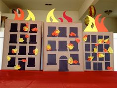 Simple burning buildings. Shoe box lids covered in brown paper from work, construction paper flames and tissue paper in the windows.