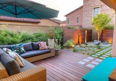 terrasse en bois composite avec canapé en osier, petit jardin sec et allée en carreaux et gazon