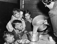 Social worker Rev S W McKibbin pouring soup for the children of the Kemp family in Erskineville Sydney whose father is unemployed due to the coal...