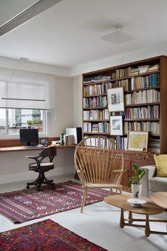 No ambiente do escritório, um antigo buffet do cliente foi usado para fazer a base fechada da estante entre o sofá e a bancada de trabalho. Cadeira de escritório com rodinhas, modelo Sherlock, assinada por Etel Carmona para a loja Arquivo Contemporâneo. Os tapetes orientais iranianos fazem parte do acervo do morador