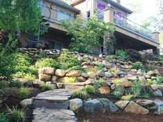 Natural Stone Stairway: An unused back slope is converted into usable space thanks to natural looking winding flagstone stairs and boulder planters. From HGTV.com's Garden Galleries