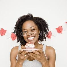 African woman holding cupcake