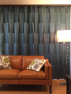 カーテンの施工例 皮のソファの背面に大胆な柄のフラットカーテンでポイントクロスのように 使用生地:D-9002/SUMINOE