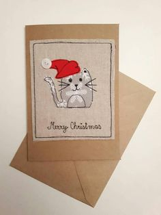 Fabric Christmas greeting cards with Cat or Snowman appliqueI have used red button for snowmans nose and white button for cats hat. I have created these design using free machine embroidery and appliqué and attached it on brown paper cards. The cards have fabric applique on the