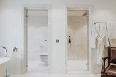 Ganzglas-Duschtüre mit transparentem Glas. Glanzverchromte Beschläge. Weisser Marmor. Eine Ganzglasdusche verzaubert die Atmosphäre im Badezimmer. Sie schenkt Klarheit und Frische - und ihre Transparenz ist eine Aussage für modernen Lebensstil.  Ihre Leichtigkeit öffnet Räume zum Träumen. Vom frühen Morgen bis abends spät. Alcove, Bathtub, Wellness, Bathroom, Glass Building, White Marble, Lifestyle, Mornings, Bathrooms