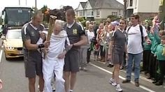 BBC News - Olympic torch carried by determined Parkinson's patient. Andy Seward, 67, who has Parkinson's Disease gets out of his wheelchair to carry the Olympic flame through Braunton.
