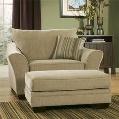 classic creamy oversized accent chair with stripe patterned cushion and footrest on stripe patterned area rug