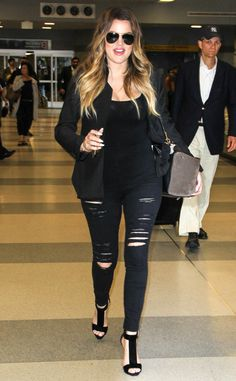 The Keeping Up With the Kardashians star rocks a stylish all-black ensemble with ripped jeans while making her way through JFK airport in New York City.