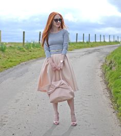 pink bow bag with pink skirt, grey sweater and pink high heels