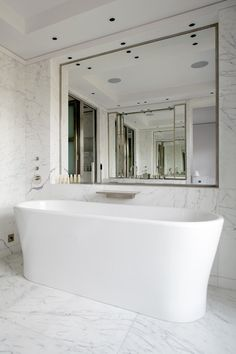 This bathroom has Statuario Marble tiled walls and floors. The modern oval freestanding bathtub ...