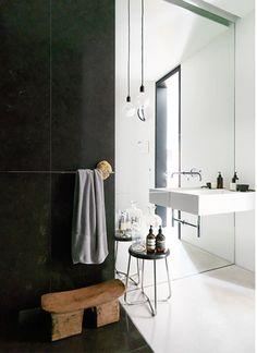 Combinación en este baño minimalista de acabados con mármol negro y espejo, con un acento rústico (banco de madera).