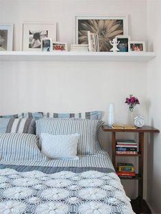 Para exibir várias fotografias, a prateleira fixada sobre a cama de casal cumpre bem a função. Todos os quadros (Fast Frame) ficam apoiados na parede e podem ser trocados facilmente. Os porta-retratos são da Tok e o enxoval da Trousseau. Projeto da decoradora Maristela Gorayeb.