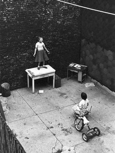 William Gale Gedney, Girl standing on desk in courtyard,...