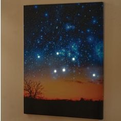 A large, colorful photo of a star-strewn sunset is already dazzling. Push the button and it's ooh-aah time. Six LED lights hidden within glow brightly. Push the button again and they twinkle. Printed canvas is gallery-wrapped on wood stretchers with sawtooth hanger on back. Takes 2 AA batteries (not included). 24' x 32'. No gift box.