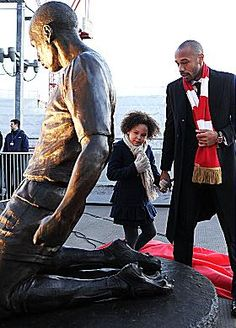 IS STATUE DADDY? ... legend Thierry and daughter Tea look at his statue