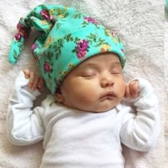 Made to order baby knot hat made out of amazing colors of purple, coral pink, chartreuse green flowers and roses on a pretty aqua green blue background cotton jersey blend knit. Fabric has a very smoo