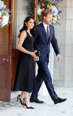 Meghan wore a chic black dress teamed with heels by Aquazzura, and an elegant clutch from ...