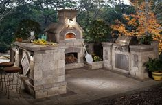 Summer Entertaining…  Outdoor kitchen featuring a brick oven, grill and bar.
