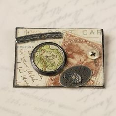 Collage brooch (with Africa stamps) | oxidised silver, postcard, stamps, map, perspex, gold | by Clare Hillerby