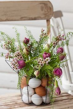 Easter Centerpiece with Eggs and Flowers. Place flowers in a vase inside wire basket and arrange plastic eggs in between. It's perfect for an elegant Easter table display. http://hative.com/creative-easter-party-ideas/
