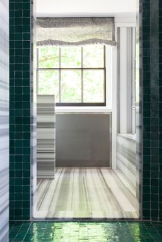 striped marble and green tiled bathroom