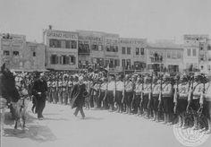 """Κατάβασις εις τον λιμένα Χανίων."""" [Στρατιωτικό άγημα αποδίδει τιμές στον απερχόμενο Διοικητή της νήσου. Ο Στέφανος Δραγούμης διετέλεσε Γενικός Διοικητής Κρήτης από τις 12 Οκτωβρίου 1912 έως τον Ιούνιο του 1913."""