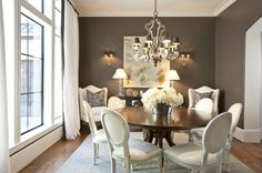 dining rooms - chic elegant French white leather Louis dining chairs walnut round dining table white curtains brown silk ribbon trim white wingback chairs Restoration Hardware glass column lamps brown purple pillows- wall color?