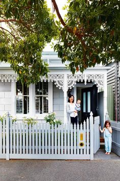 Pale blue/grey Victorian heritage cottage with white iron lacework/fretwork, picket fence