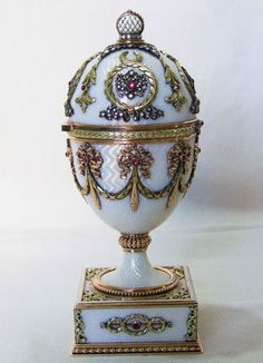 Faberge Egg, ca. 1896 ~ This egg is covered in white, translucent enamel over a guilloché ground and is decorated in four-colored gold, diamonds and rubies.
