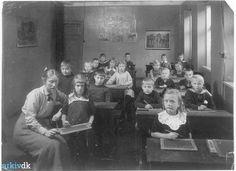 Elever i et klasselokale   Elever i et klasselokale i Giersing  Realskole. Eleverne sidder bag deres  pulte og skriver på deres tavler med  griffel.  Lærerinden ses i forreste venstre  hjørne ved en elev. 1918