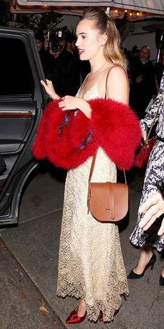 Suki Waterhouse wears a lace slip dress, red fur stole, red heels, and a saddle bag