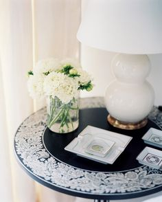 Square porcelain dishes atop a round side table.