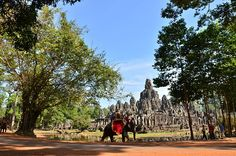 People Riding On Elephant Outside Bayon Temple Against Sky