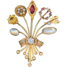 Victorian Gold Moonstone and Diamond Flower BroochbrThis graceful Victorian bouquet of flower brooch is alluring. It dates from the 1800's. It s set in 14k yellow gold. The enchanting bouquet of ruby, diamond, citrine, moonstone, garnet and pearl flowers is exquisitely wrapped in a yellow gold bow tied with a knot sealed with .65 ct old European cut diamond. The diamond is H in color and VS2 in clarity. The pin weighs 15.47 grams. It measures 2' x 1 1/2' at it widest point. A distinct of Victorian Life, Victorian Gold, Diamond Flower, Diamond Cuts, Gold Bow Tie, European Cut Diamonds, Antique Engagement Rings, Flower Brooch, Garnet