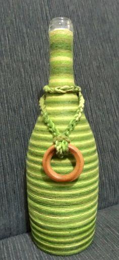 Linda garrafa de vidro revestida com barbante e pingente de argola de madeira.