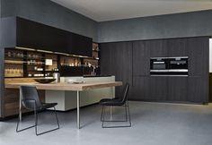 Il piano della cucina Phoenix di Varenna Poliform è in noce. Le sedie Ventura con scocca in pelle e struttura in metallo laccato opaco carbone